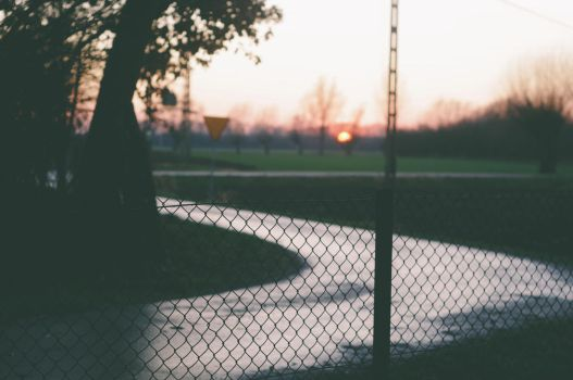 one with sunset behind a fence by Maclunar