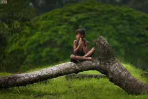 Young boy praying while sitting on a dead tree by LordRobin3K