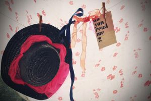 a hat a bow and a postcard by Holunder
