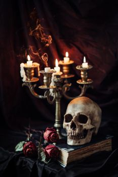 Human skull on book with antique candlestick by Black-Bl00d